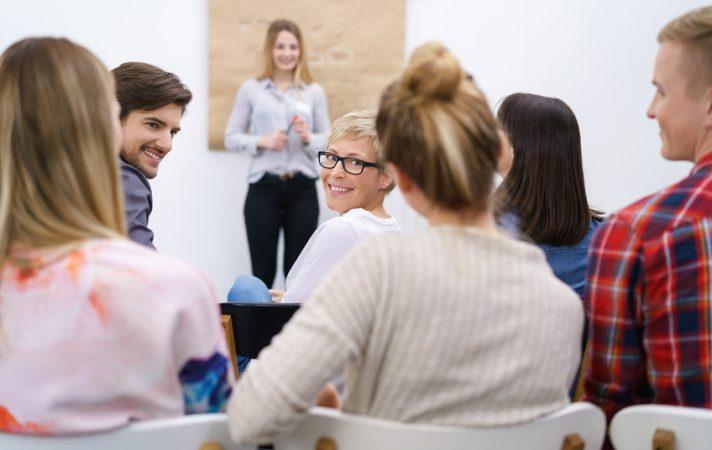 teilnehmer in einem vortrag schauen lächelnd über die schulter zurück