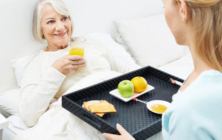 Alte Frau bekommt Frühstück ans Bett geliefert von ihrer Enkelin